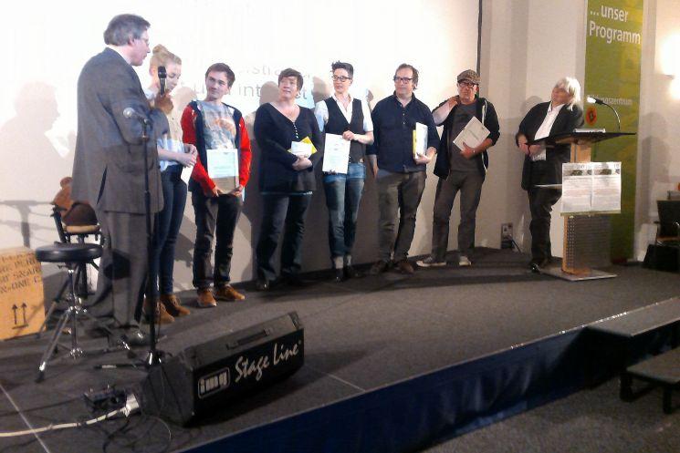 Gewinner anderer Katogorien des Alternativen Medienpreises. ganz links Moderator und Organisator Peter Lokk. Ganz rechts: Mitorganisatorin Gebriele Hooffacker.